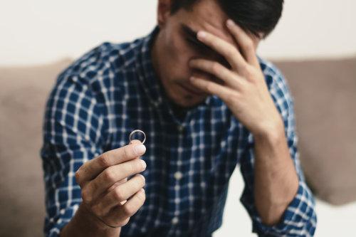 Cierpiący mężczyzna z obrączką w dłoni myśli o zakończonym związku