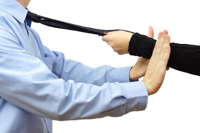 Ręka kobiety ciągnie za krawat mężczyzny, a mężczyzna się opiera