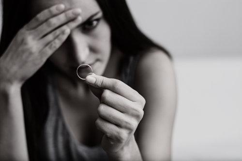 Zamyślona, cierpiąca kobieta trzyma w dłoni obrączkę