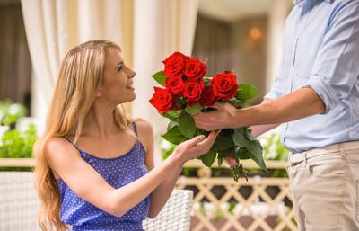 Mężczyzna daje kobiecie bukiet róż