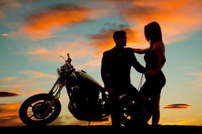 Motocykl, mężczyzna i kobieta na tle zachodzącego słońca