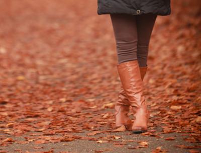 Kobiece nogi w brązowych kozakach, jesienna pogoda