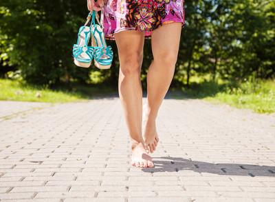 Kobieta idąca na bosaka i trzymająca buty w ręku