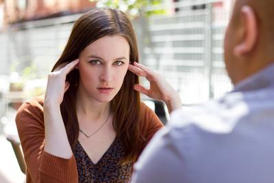 Para rozmawiająca przy stoliku, kobieta zatyka uszy