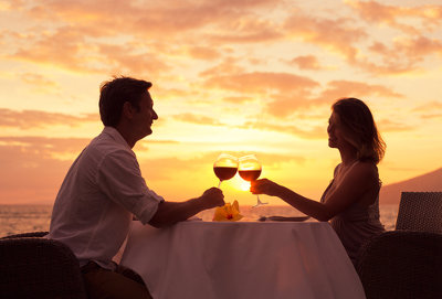 Kobieta i mężczyzna siedzą przy stole i piją wino, na tle zachodzącego słońca