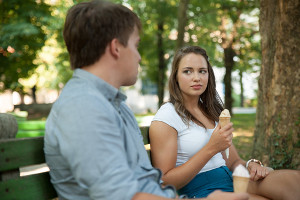 Ch�opak i dziewczyna siedz�cy na �awce i jedz�cy lody