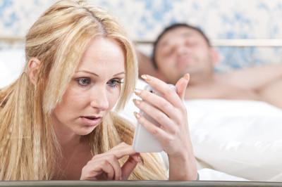 Para leżąca w łóżku, kobieta patrząca w telefon