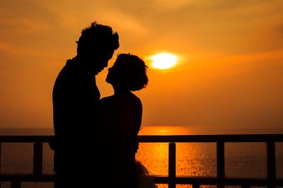 Przytulająca się para na tle zachodzącego słońca